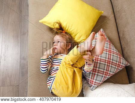 A Little Girl In Yellow Trousers And A Bright T-shirt Is Lying On Her Back On The Sofa With Her Legs