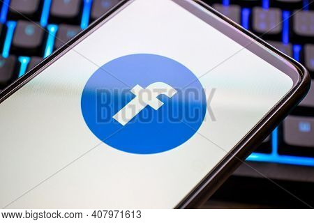 Mobile Phone With Blue Facebook Logo On Display And Colorful Illuminated Keyboard. Smartphone Concep