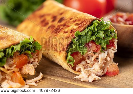 Closeup Of Chicken Burritos With Lettuce And Tomato On A Wooden Cutting Board