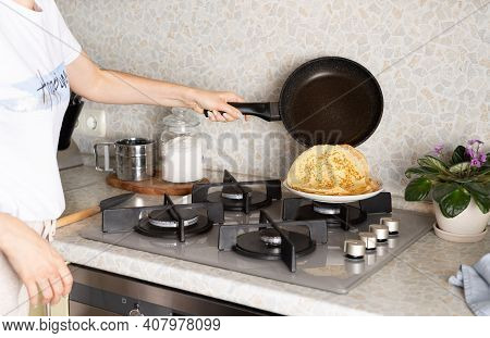 Woman Puts Hot Pancake From Frying Pan Onto Stack Of Freshly Baked Pancakes. The Process Of Making T