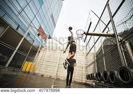 Young Asian Basketball Player Dunking The Ball On Outdoor Court