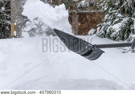 Somebody Is Throwing Snow With A Black Plastic Shovel, Snow Removal Tool, Shoveler Cleaning Snow Out