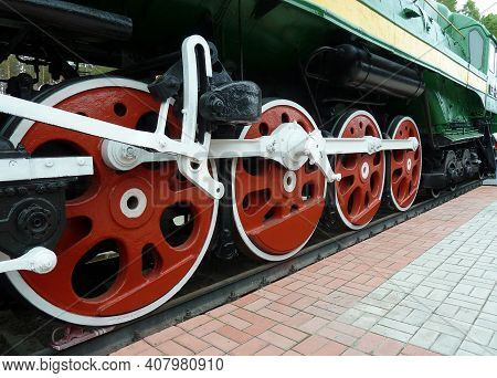 Red Driving Wheels Of A Steam Locomotive, Connected By Levers. Old Locomotive Close-up.