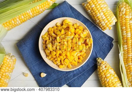 Tasty Sweet Corn Kernels In Bowl And Fresh Cobs On White Wooden Table, Flat Lay