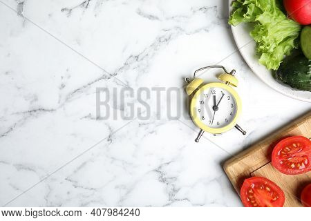 Alarm Clock And Vegetables On White Marble Table, Flat Lay With Space For Text. Meal Timing Concept