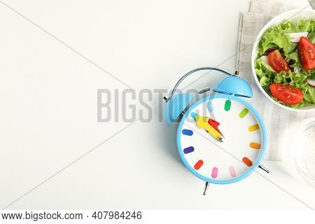Alarm Clock And Salad On White Background, Top View. Meal Timing Concept