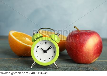 Alarm Clock, Orange And Apple On Light Blue Wooden Table. Meal Timing Concept