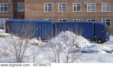 Big Blue Truck. Trucking Industry. Building Under Construction. Winter Snow. Kazakhstan (ust-kamenog