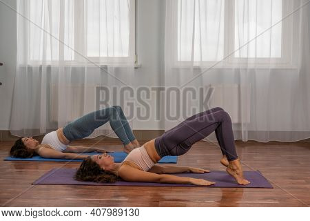 Two Young Womans Fitness Instructor In Violet Sportswear Leggings And Top Stretching In The Gym Befo