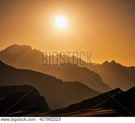 Sun Glow In Evening Hazy Sky And Mountain Silhouettes View.  Peaceful View From Giau Pass. Climate,