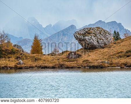 Overcast Morning Autumn Alpine Dolomites Mountain Scene. Peaceful Valparola Pass And Lake View, Bell