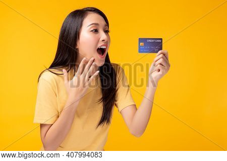 Young Asian Woman Showing Plastic Credit Card And Looking At Credit Card With Excited And Surprised
