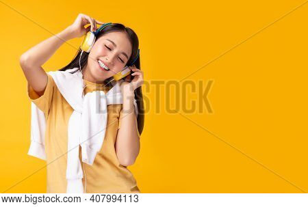 Happy Young Asian Woman Listening Music In Headphones And Dancing Over Yellow Background Charming Gi