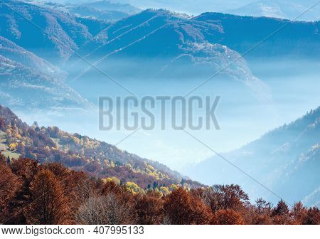 Morning Fog In Autumn Carpathian And Colorful Forest On Slope.