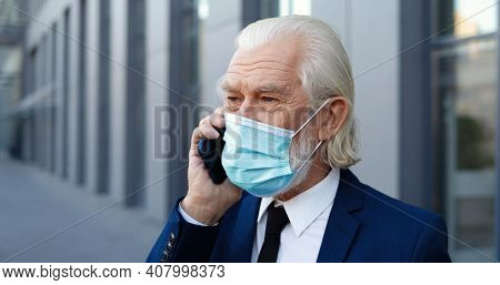 Close Up Of Caucasian Old Good-looking Gray-haired Man In Medical Mask Talking On Mobile Phone Outdo