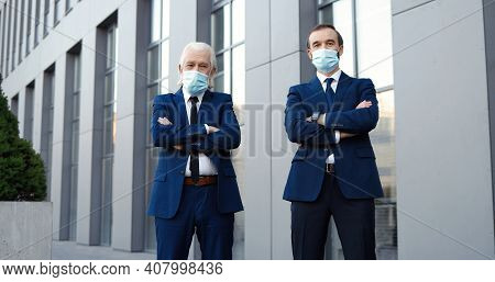 Two Caucasian Males Business Partners In Suits And Ties And Medical Masks Standing Outdoors, Looking