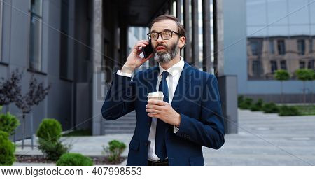 Caucasian Middle-aged Man In Glasses Walking Outdoor, Talking On Mobile Phone And Drinking Coffe To-