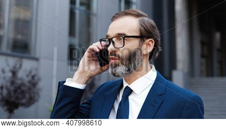 Caucasian Middle-aged Man In Glasses Talking On Mobile Phone And Drinking Coffe To-go In Morning Out