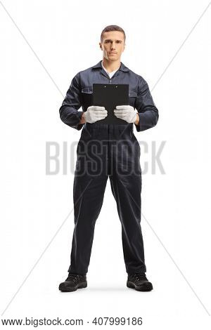 Full length portrait of a mechanic in a uniform standing and holding a document with a clipboard isolated on white background
