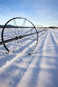 A snow covered farm field with an irrigation pipe and wheels on the Rathdrum Prairie in northern Idaho. poster