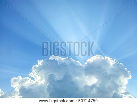 The sun is hiding behind a cumulus cloud towards clear blue sky poster