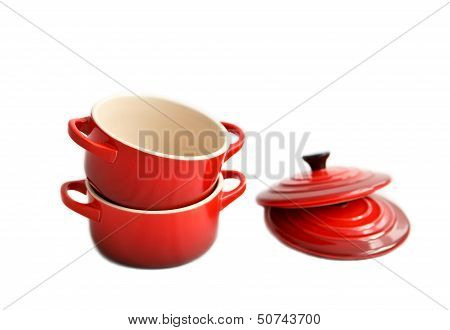 Two red cocottes (small casserole) with covers on a white background