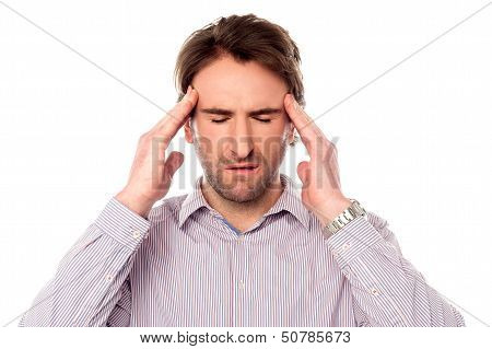 Man suffering from headache wincing over white poster
