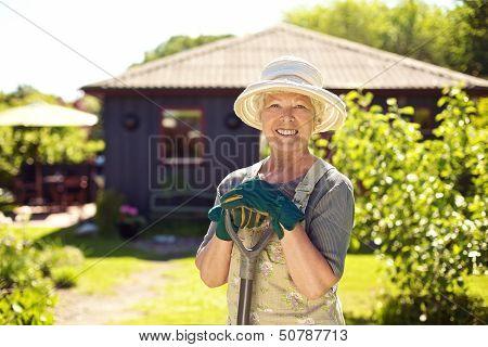 Cheerful Elder Woman With Gardening Tool In Backyard