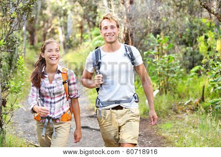 Outdoor activity couple hiking - happy hikers walking in forest. Hiker couple laughing and smiling. Multiracial group, Caucasian man and Asian woman on Big Island, Hawaii, USA.
