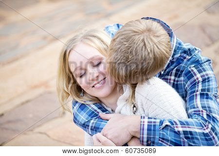 Young White Male Kissing His Fiance In Her Neck