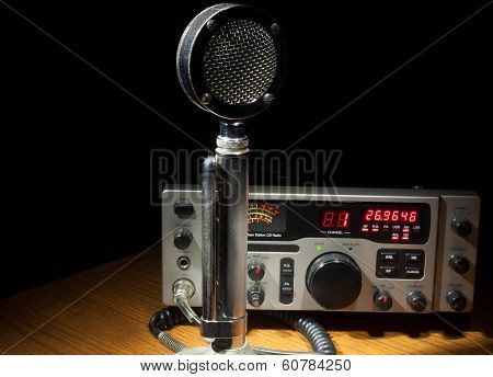 Two way radio on a table with an old metal microphone poster