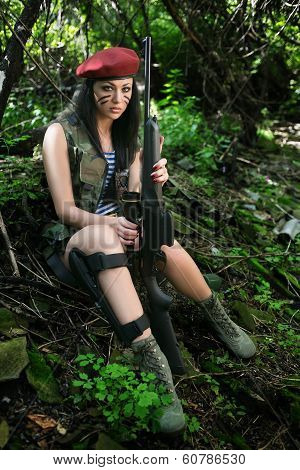 girl with a rifle in the woods