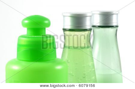Three different green cosmetic bottles on white background poster