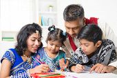 Asian Indian family drawing and painting picture at home. India family lifestyle. Happy parents and children having fun. poster