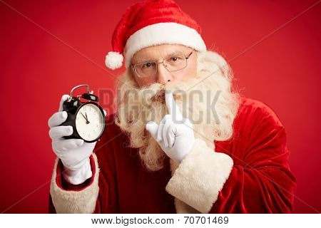 Santa Claus holding clock showing five minutes to midnight and making shhh gesture poster