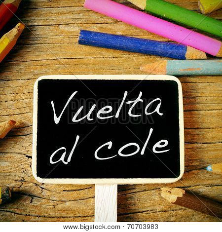 the sentence vuelta al cole, back to school written in spanish in a blackboard label, on a wooden desk and colored pencils of different colors