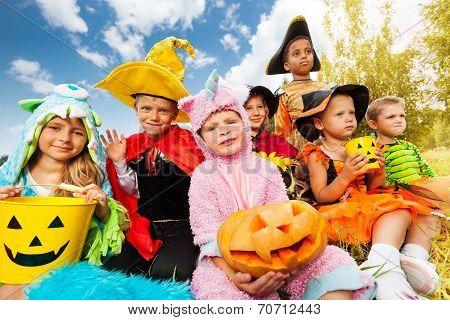 Halloween kids in beautiful costumes sitting