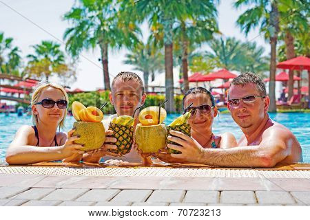 Friends celebrating holidays with exotic drinks at the pool