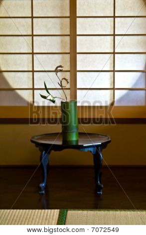 A White Rose In A Bamboo Vase Against A Japanese Paper Screen Window