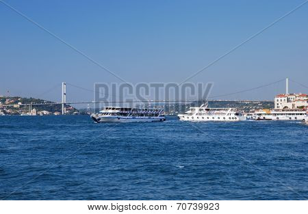 ISTANBUL, TURKEY - AUGUST 8, 2007: Ferry boats traverse the strait against the Bosporus bridge. For thousands locals and tourists, the ferry is the fastest and cheapest way to traverse Bosporus strait