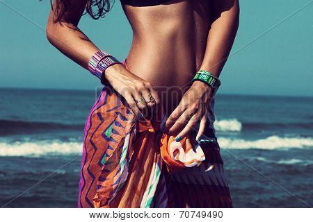 young woman on beach tiedown colorful sarong wearing beautiful braceletes closeup