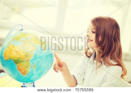 education and school concept - smilng little student girl with globe at school
