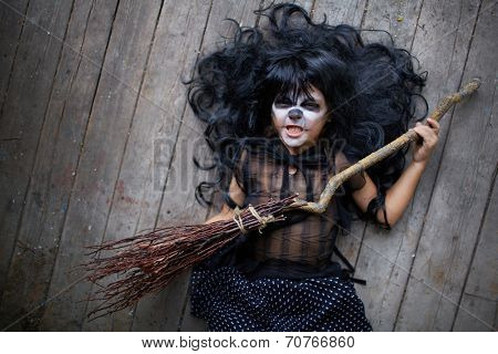 Grinning girl in black wig holding broom and looking at camera