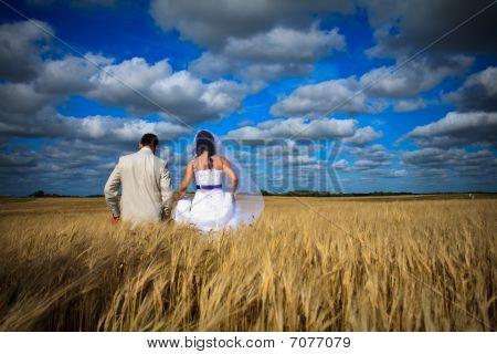 Wedding Couple Against Blue Sky Among Rye Field Simbolizing Fertility