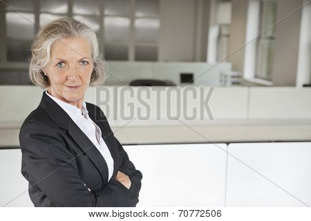 Portrait of confident senior businesswoman with arms crossed in office