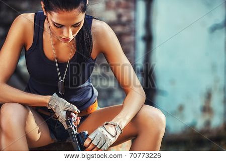 sexy brutal woman sitting and holding handgun