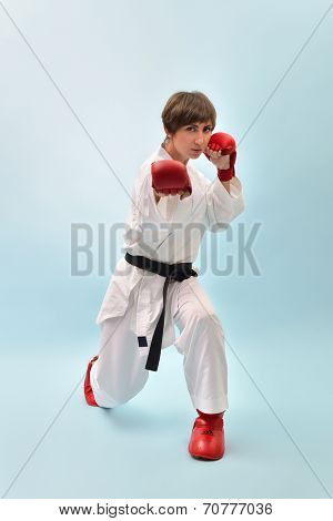 fighting karate girl, young woman with black belts - champions of the world, over blue background studio shot