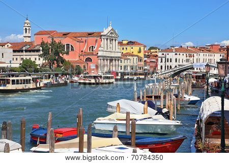 VENICE, ITALY - SEPTEMBER 9, 2010: Tourists on gondolas and vaporetto on the Grand Canal.  Pier for boats and gondolas