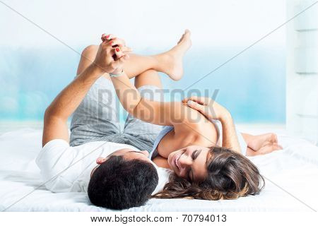 Young Couple Showing Affection In Bedroom .