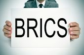 man wearing a suit holding a signboard with the word BRICS, for the five major emerging national economies Brazil, Russia, India, China and South Africa, written in it poster
